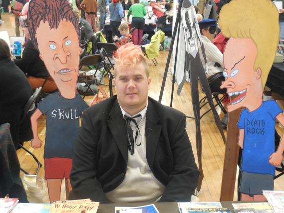 Rick's table at the Portland Comic Expo being watched by Richard Hale. Note Beavis and Butt-Head in the background.