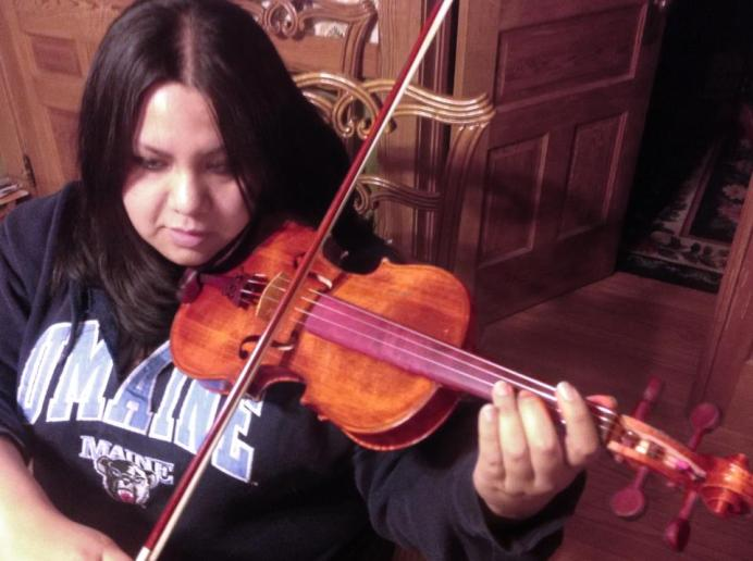 Alex playing a violin her father made for her.